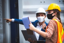 executives businessmen, and engineers or foreman wear medical face masks. Quality Control Officer inspecting warehouses at containers yard for international shipping businesses