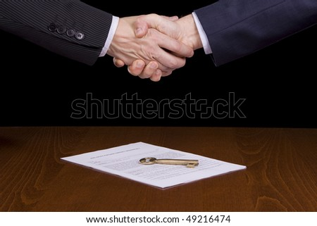 Executives handshake over a contract and a golden key