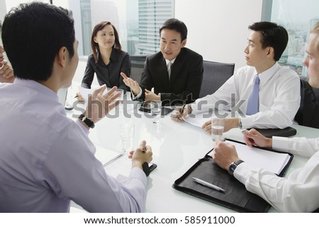 Executives having a discussion around conference table