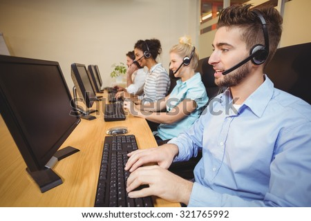 Executives working in call center wearing headsets