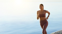 Exercise And Sport. Beautiful female runner jogging on the beach, copy space, banner