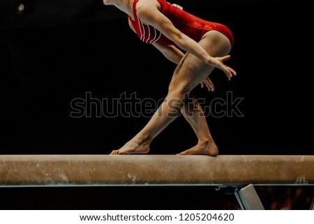exercise balance beam female gymnast on black background