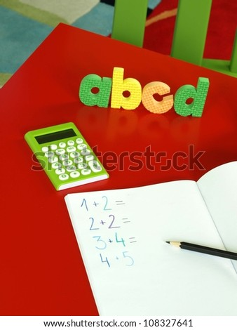 Exercise book, calculator, and colorful letters from alphabet