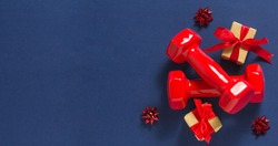Exercise, fitness and development of the concept of a happy Christmas and a happy New year. Red dumbbells, bows and gifts with red ribbons on a dark blue background.