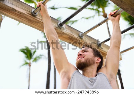 Exercise fitness athlete exercising on monkey bars. Crossfit man working out arms swinging on brachiation ladder as strength training crossfit routine.