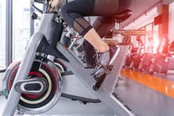 Exercise ride a stationary bike cardio machine weight loss after workout at fitness gym of woman sporty aerobic for slim and firm healthy lifestyle bodybuilding.