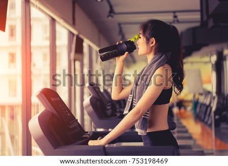 Exercise treadmill cardio running workout at fitness gym of woman taking weight loss with machine aerobic for slim and firm healthy in the morning with drinking protein shake.