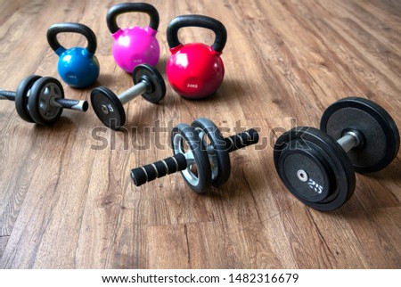 exercise weights - dumbbells with extra plates , kettle bells, Ab roller wheels on wooden floor in ygm, weight lifting and weight loss concept