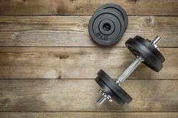 exercise weights - iron dumbbell with extra plates on a wooden deck