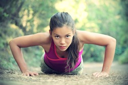 Exercise woman doing push-ups outdoors in the forest, Beautiful young female athlete.