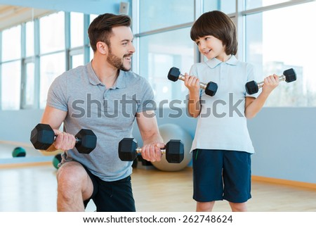Exercising together. Happy father and son exercising with dumbbells and smiling while standing in health club