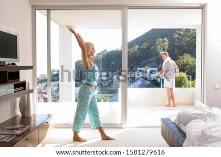 Exercising woman stretching arms in bedroom in yoga pose