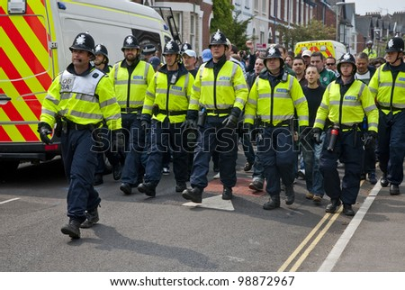 EXETER - APRIL 30: Devon and Cornwall Police escort football fans to prevent football violence at the League 1 match between Exeter City FC and Plymouth Argyle FC on April 30, 2011 in Exeter, UK.