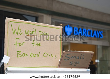 "EXETER - FEBRUARY 11: A sign saying ""We won't pay for the bankers crisis"" in front of the Exeter branch of Barclays bank on February 11, 2012 in Exeter, UK."