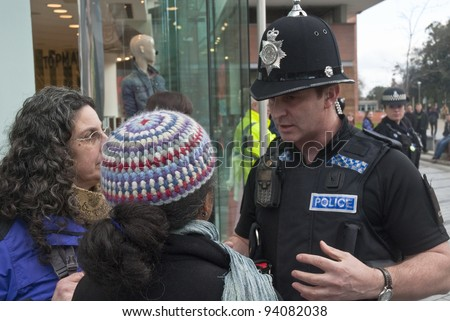EXETER - JANUARY 28: Devon & Corwall police officers confronts two Occupy Exeter activists during their direct action outside the Exeter branch of Topshop  on January 28, 2012 in Exeter, UK