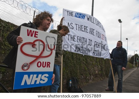 "EXETER - MARCH 7:  Activist Bruce Chapman holds a placard that says ""We Love our NHS"", during the NHS reform protest outside the Royal Devon & Exeter Hospital on March 7, 2012 in Exeter, UK"