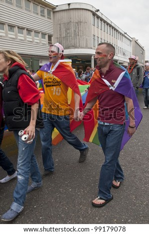 EXETER - MARCH 31: Festival goers hold hands and the rainbow banner at the Exeter Pride 2012 Parade in Exeter City centre on March 31, 2012 in Exeter, UK