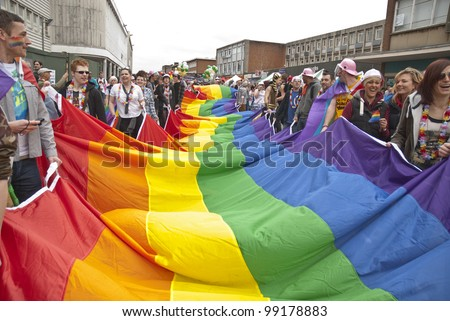 EXETER - MARCH 31: Festival goers hold the rainbow banner at the Exeter Pride 2012 Parade in Exeter City centre on March 31, 2012 in Exeter, UK