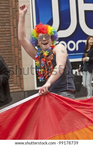 EXETER - MARCH 31:  Festival goers with painted faces hold the rainbow banner at the Exeter Pride 2012 Parade in Exeter City centre  on March 31, 2012 in Exeter, UK