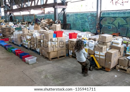 EXETER - MARCH 14: Sakeenah Feghir from BookCycle UK pulling a pallet of books to the container bound for Ghana at the Bookcycle UK warehouse on March 14, 2013 in Exeter, Devon, UK - stock photo