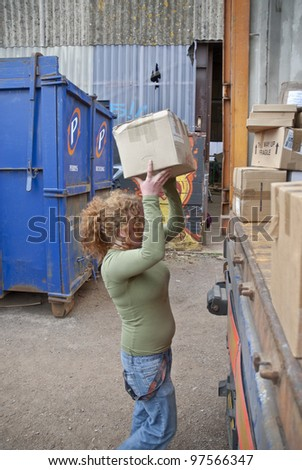 EXETER - MARCH 9: Volunteer from BookCycle loads the last box of books into the container that is taking donated book to Ghana on March 9,  2012 in Exeter.