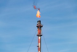 Exhaust chimney of the petrochemical industry with the burning flame of Palos de la Frontera in Huelva, Andalusia, Spain.
