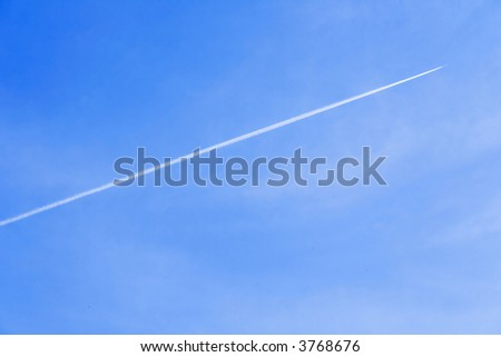 Exhaust trail seen behind a aircraft very high in the sky.