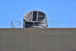 Exhaust ventilation air hole in rooftop of industrial building with blue sky background