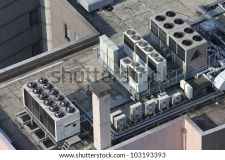 Exhaust vents of industrial air conditioning and ventilation units. Skyscraper roof top in Tokyo, Japan.