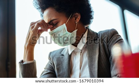 Exhausted African American businesswoman with face mask having a headache while sitting in a cafe.