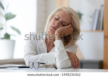Exhausted aged woman worker sit at office desk fall asleep distracted from work, tired senior businesswoman feel fatigue sleeping at workplace taking break dreaming or visualizing