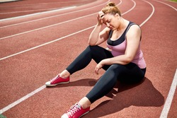 Exhausted and desperate plump woman sitting on stadium racetrack