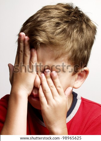 exhausted and sad little kid portrait,rubbing his eyes. - stock photo