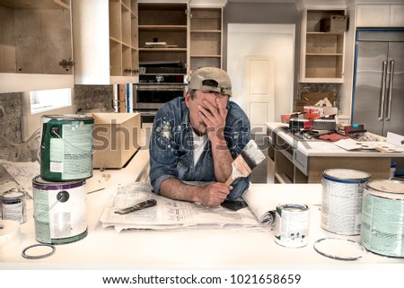 Exhausted and tired male painter in painter's clothes, face in hands holding wet paint brush in cluttered home kitchen surrounded with dripping paint cans and unfinished cabinets behind him