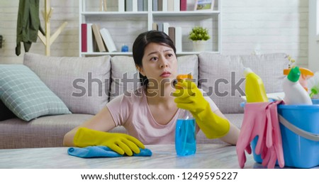 Exhausted asian housewife looking outside the house from window to the urban city view. young lady sitting on floor resting while doing housework wiping table. elegant woman wearing gloves cleaning. #1249595227