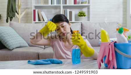 Exhausted asian housewife wiping off sweat from forehead by hands in rubber protective gloves. young lady sitting on floor holding sprayer cleaning up the table in the cozy apartment. woman frowning. #1249591903