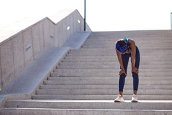 exhausted black fitness woman fizzle out, standing on stairs outdoors. after running