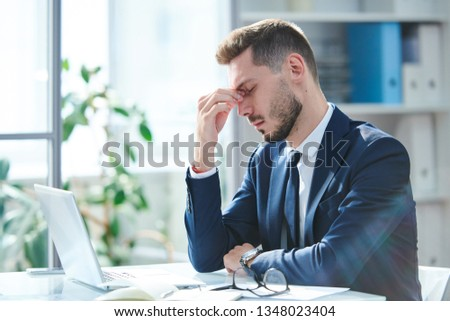 Exhausted businessman in formalwear sitting by desk in front of laptop after hard working day