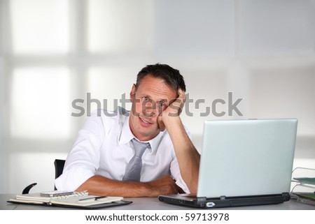 Exhausted businessman in front of computer desk