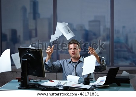 Exhausted businessman throwing documents into air sitting at office desk in overtime. - stock photo