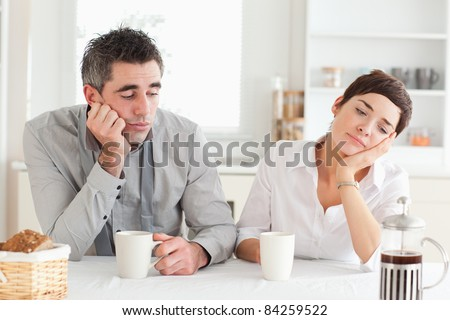 Exhausted couple drinking coffee in a kitchen