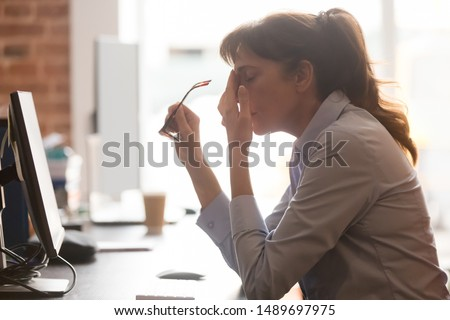 Exhausted female worker sit at office desk take off glasses feel unwell having dizziness or blurry vision, tired woman employee suffer from migraine or headache unable to work. Health problem concept