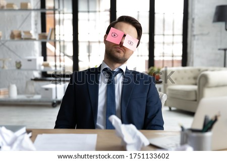 Exhausted male employee sit at desk with stickers on eyes fall asleep nap at workplace, tired businessman or boss sleeping in office, overwhelmed with work, feel fatigue exhaustion, overwork concept