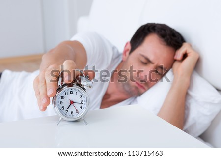 Exhausted Man Being Awakened By An Alarm Clock In His Bedroom