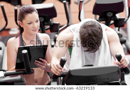 Exhausted man doing exercises while his coach is looking at his results in a sport centre