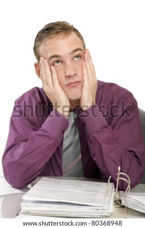 Exhausted man in the office with files on. He keeps his hands to his face and sad looks up