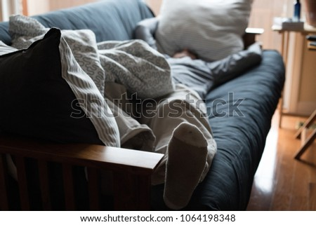 Exhausted man napping on a couch with his head under a pillow. #1064198348