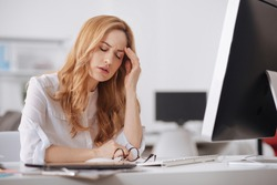 Exhausted manager suffering from chronic daily headaches in the office