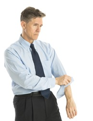 Exhausted mature businessman rolling up his sleeves while standing isolated over white background