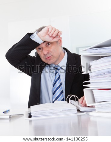 Exhausted Mature Businessman Surrounded By Files At Desk